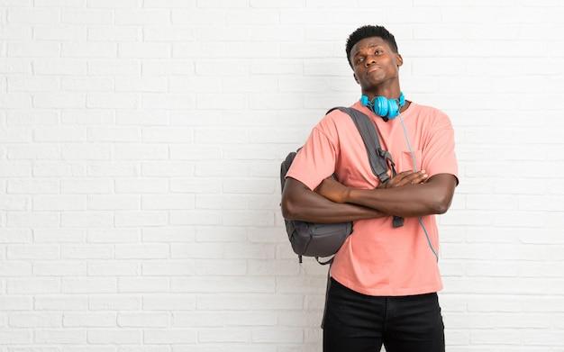 Junger afroer-amerikanisch mannstudent, der unwichtige und zweifelgeste beim anheben der schultern macht