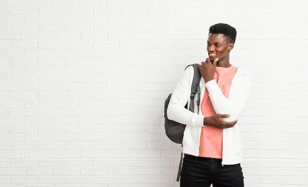 Junger afroer-amerikanisch mannstudent, der zur seite mit der hand auf dem kinn steht und schaut