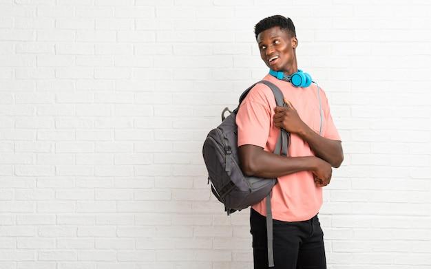 Junger afroer-amerikanisch mannstudent in seitlicher stellung beim schauen über der schulter mit einem lächeln