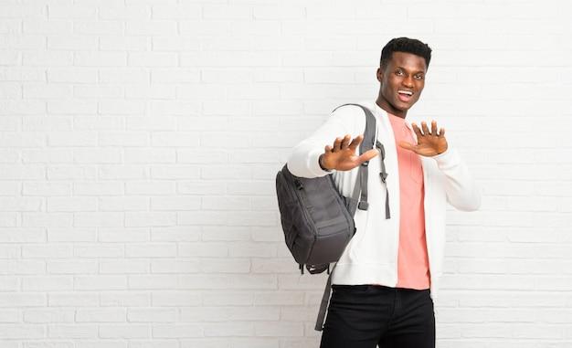 Junger afroer-amerikanisch mannstudent ist ein kleines bisschen nervös und erschrocken, hände an die front ausdehnend