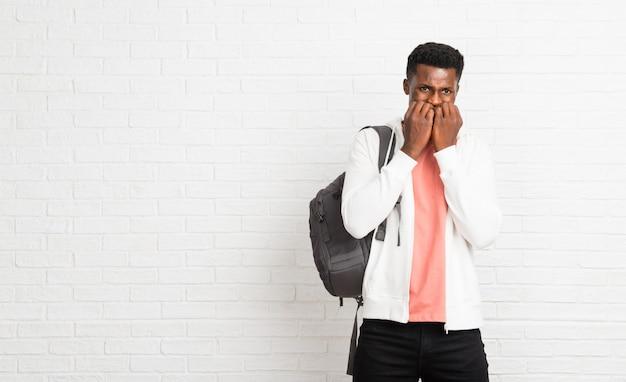 Junger afroer-amerikanisch mannstudent ist ein kleines bisschen nervös und erschrocken, hände zum mund setzend