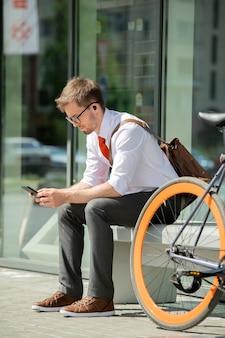 Junger agent in der abendgarderobe, der im smartphone rollt, während auf bank durch geschäftszentrum sitzt und auf kunden in städtischer umgebung wartet