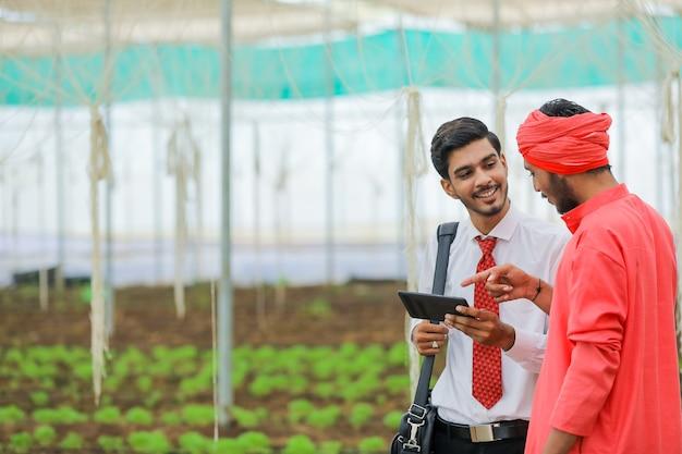 Junger agronom, der einige informationen zum landwirt im smartphone am gewächshaus zeigt