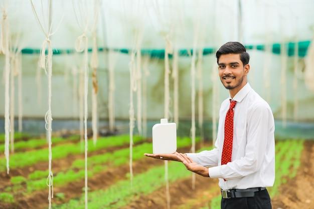 Junger agronom, der flasche in der hand am gewächshaus hält