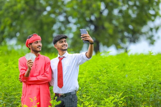 Junger agronom, der selfie mit indischem landwirt auf der grünen wiese nimmt
