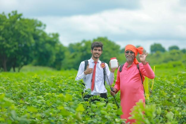 Junger agronom mit landwirt, der düngerflasche im feld zeigt