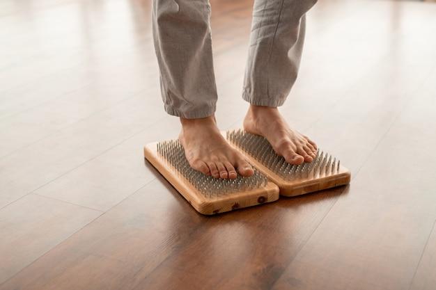 Junger aktiver barfußmann in sportspants, die auf yoga-therapiekissen mit metallischen borsten stehen, während entspannungsübungen üben
