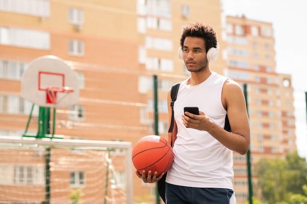 Junger aktiver mann mit ball, der musik in kopfhörern von der wiedergabeliste beim stehen auf spielplatz hört
