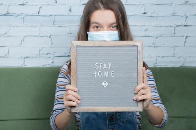 Junger aktivist mit einem plakat im zusammenhang mit dem covid-virus