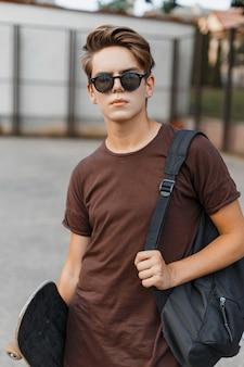 Junger amerikanischer hipster-mann in der schwarzen trendigen sonnenbrille in einem trendigen t-shirt mit einem sportlichen schwarzen rucksack mit einem skateboard, das auf dem basketballplatz steht
