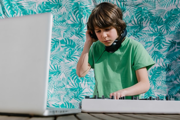 Junger amerikanischer junge in der nähe des dj-controllers - das konzept des djing