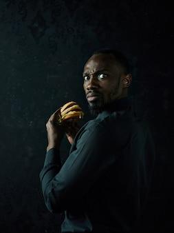 Junger amerikanischer mann, der hamburger isst und weg auf schwarzem studiohintergrund schaut