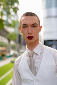 Junger androgyner geschäftsmann, der lippenstift trägt