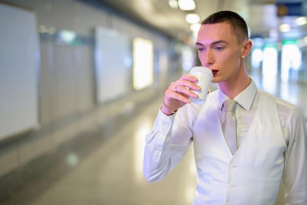 Junger androgyner homosexueller lgtb-geschäftsmann, der kaffee trinkt