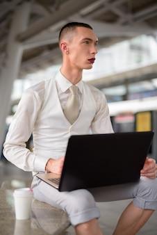 Junger androgyner homosexueller lgtb-geschäftsmann, der laptop-computer benutzt