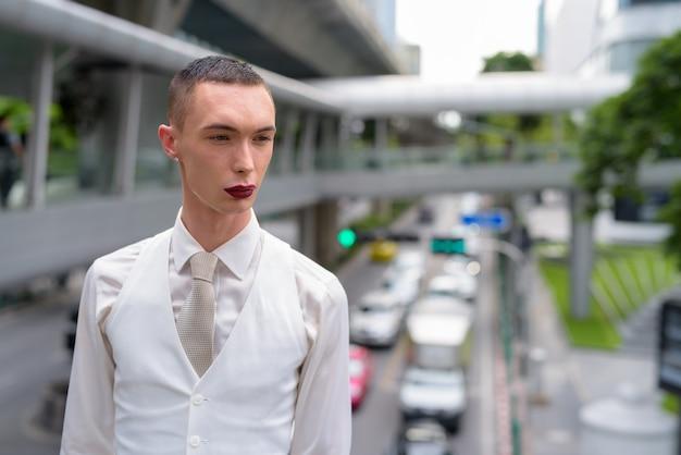 Junger androgyner homosexueller lgtb-geschäftsmann, der lippenstift trägt