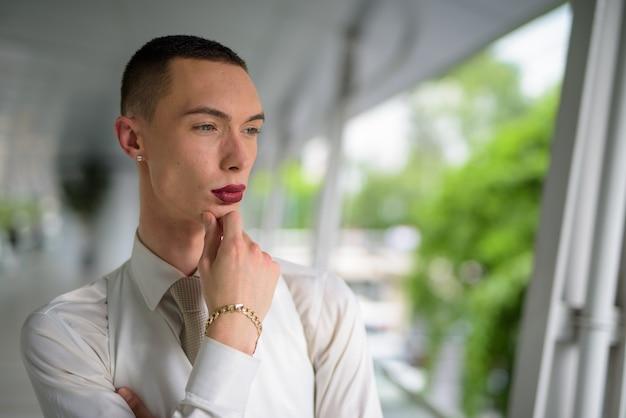 Junger androgyner homosexueller lgtb-mann, der draußen denkt