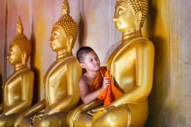 Junger anfängermönch, der buddha-statue am alten tempel in thailand scheuert
