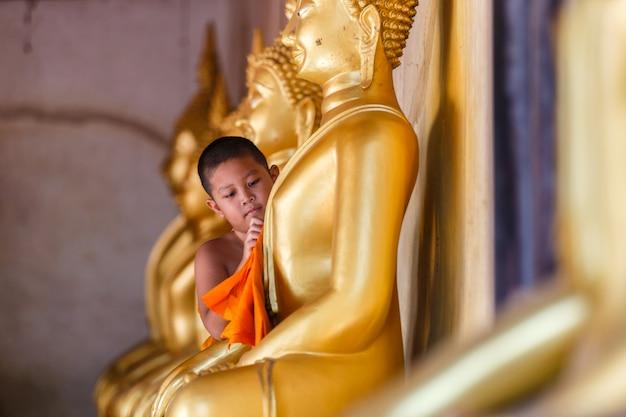 Junger anfängermönch, der buddha-statue am tempel in thailand scheuert