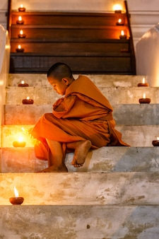 Junger anfängermönch des porträts, der im treppenhaus am alten tempel sitzt