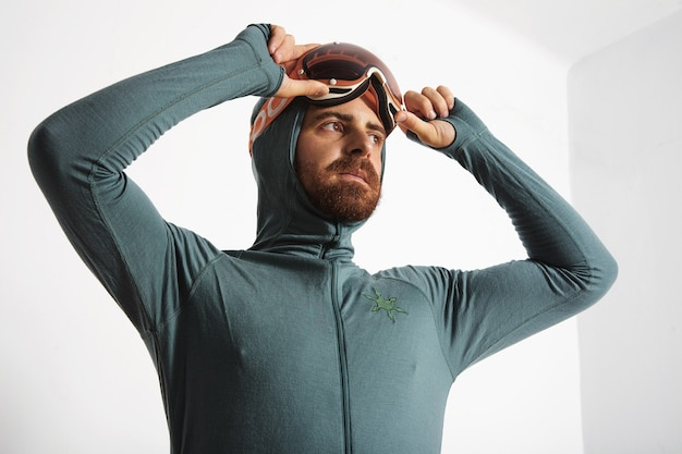Junger angepasster bärtiger männlicher athlet in der basisschicht-thermosuite mit den händen auf seiner snowboardbrille, die zur seite schaut