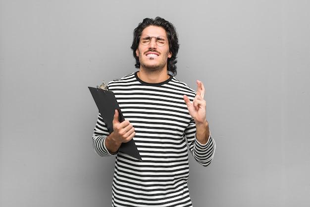 Junger angestelltenmann, der ein inventar hält, das finger für glück kreuzt