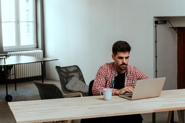 Junger angestellter, der computermonitor während des arbeitstages im büro betrachtet.