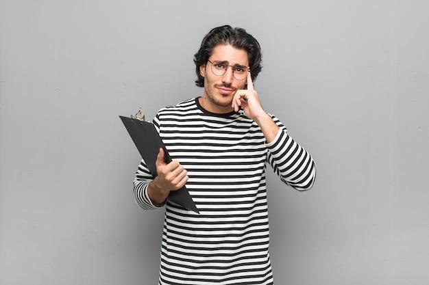 Junger angestellter, der ein inventar hält, konzentrierte sich auf eine aufgabe, zeigefinger, die kopf zeigen.