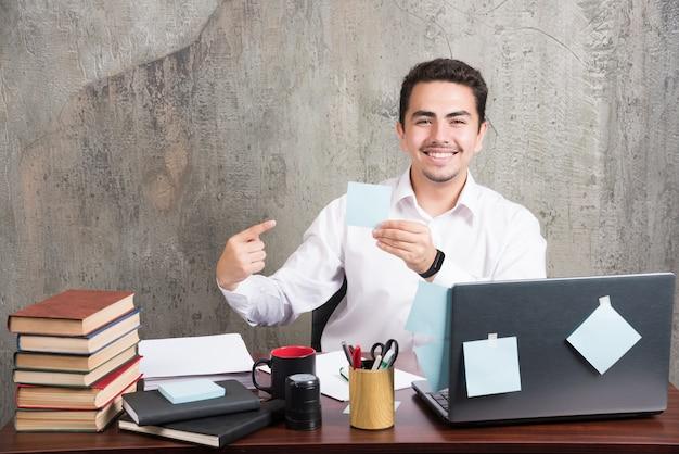 Junger angestellter, der glücklich seinen notizblock auf den schreibtisch zeigt.