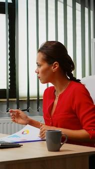 Junger angestellter, der klemmbrettinformationen überprüft, die auf pc-desktop schauen. hispanischer unternehmer, der in einem modernen professionellen büro arbeitet, arbeitsplatz in einer persönlichen unternehmensfirma, die auf der computertastatur tippt