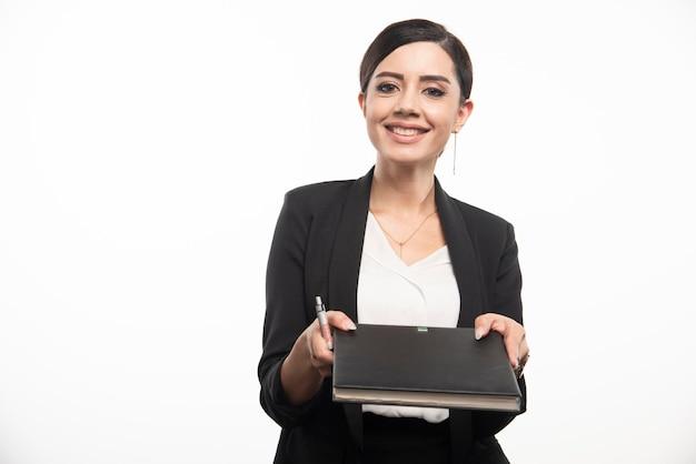 Junger angestellter, der notizbuch auf weißem hintergrund gibt. foto in hoher qualität