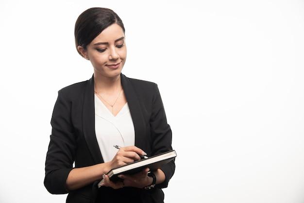 Junger angestellter, der notizbuch auf weißem hintergrund überprüft. foto in hoher qualität
