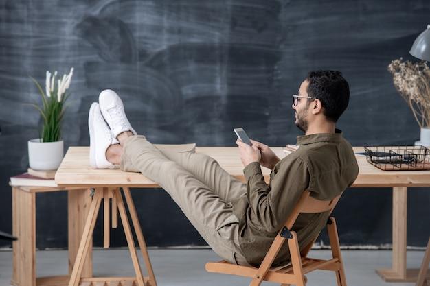 Junger angestellter in der freizeitkleidung, die beine auf tisch hält, während im smartphone durch arbeitsplatz scrollen