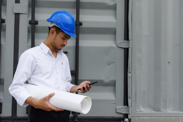 Junger arabischer bärtiger feldingenieur mit bauarbeiterhelm-text, chat, projektplan am telefon mit blaupausen-baupapier in der nähe des containers überprüfen