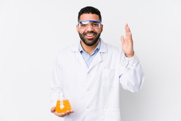 Junger arabischer chemiemann isoliert, der eine angenehme überraschung empfängt, aufgeregt und hände hebt.