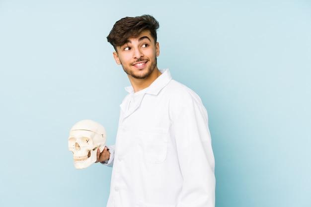 Junger arabischer doktormann, der einen schädel hält, schaut lächelnd, fröhlich und angenehm zur seite.