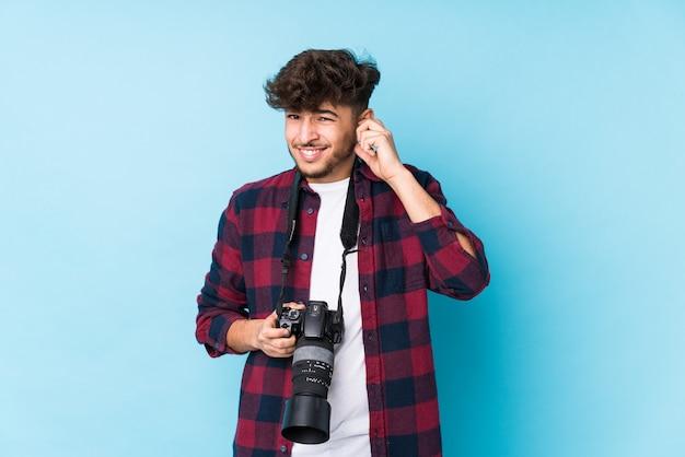 Junger arabischer fotografmann isoliert, der ohren mit händen bedeckt.