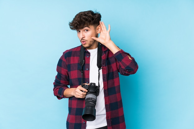 Junger arabischer fotografmann lokalisiertes versuchen zum hören eines klatsches.