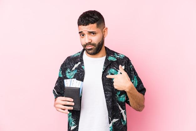 Junger arabischer kühler mann, der eine bordkarte hält, die isoliert mit dem finger auf sie zeigt, als ob die einladung näher kommt.