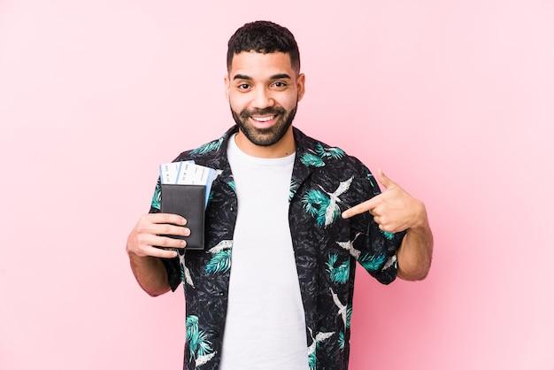 Junger arabischer kühler mann, der eine bordkarte hält isolierte person, die von hand auf einen hemdkopierraum zeigt, stolz und zuversichtlich zeigt