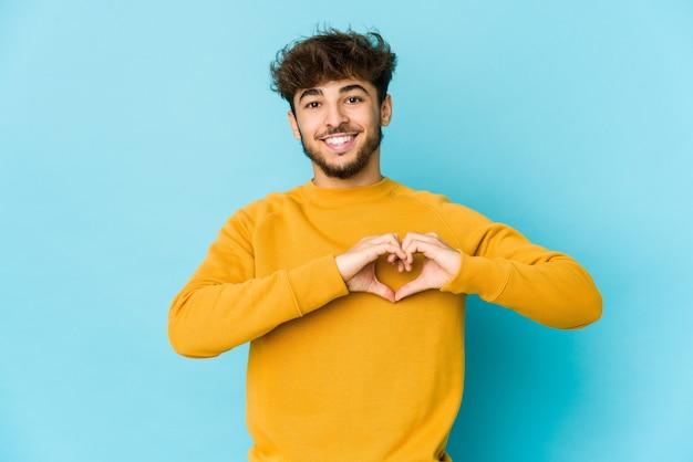 Junger arabischer mann auf blau lächelnd und zeigt eine herzform mit händen.