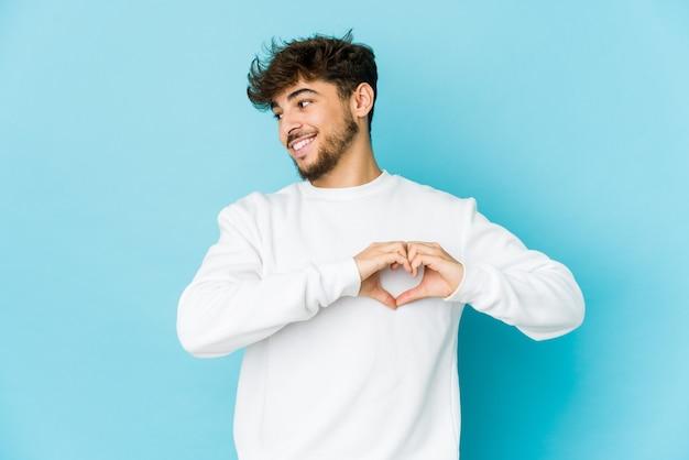 Junger arabischer mann auf blauem hintergrund lächelnd und zeigt eine herzform mit händen.