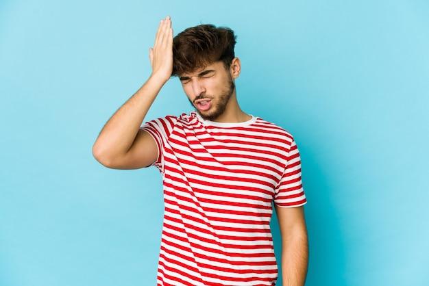 Junger arabischer mann auf blauer wand, der etwas vergisst, stirn mit handfläche schlägt und augen schließt.