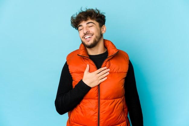 Junger arabischer mann auf blauer wand lacht laut und hält hand auf brust.