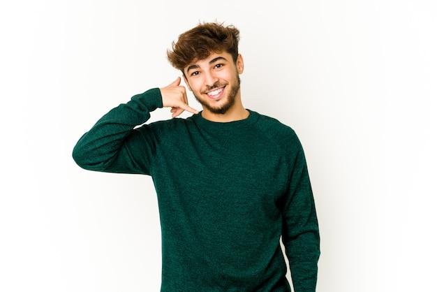 Junger arabischer mann auf weiß, der eine handy-anrufgeste mit den fingern zeigt.