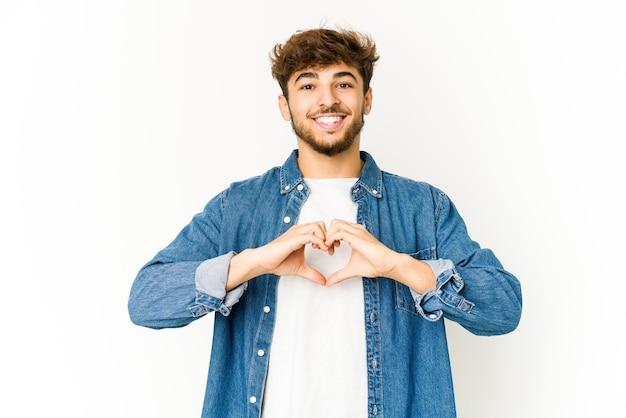 Junger arabischer mann auf weißem hintergrund lächelnd und zeigt eine herzform mit händen.