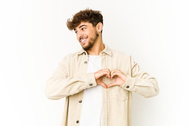 Junger arabischer mann auf weißem lächeln und zeigt eine herzform mit händen.