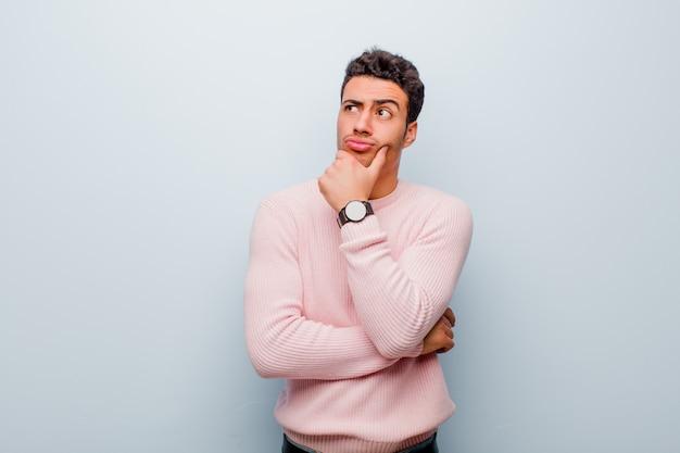 Junger arabischer mann denkt, fühlt sich zweifelhaft und verwirrt, mit verschiedenen optionen, fragt sich, welche entscheidung gegen graue wand zu treffen ist