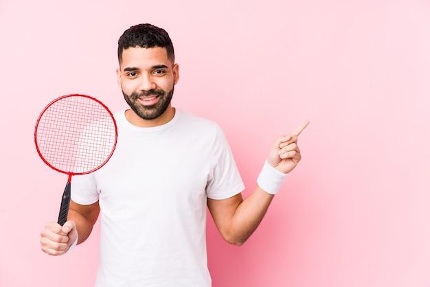 Junger arabischer mann, der badminton spielt, isolierte lächelnd und zeigte zur seite und zeigte etwas an der leeren stelle.