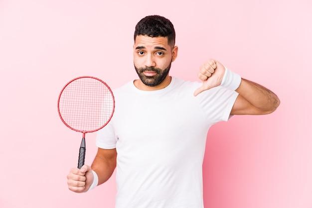 Junger arabischer mann, der badminton spielt, zeigt isoliert eine abneigungsgeste, daumen nach unten. uneinigkeit konzept.